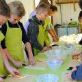 children preparing vegetables outside